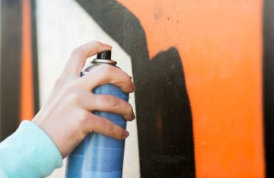 48506990 - people, art, creativity and youth culture concept - close up of hand drawing graffiti with spray paint on street wall
