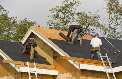39959435 - construction crew working on the roof sheeting of a new, luxury residential home project in oregon