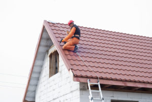47751738 - builder performs installation gable roof tiles of metal