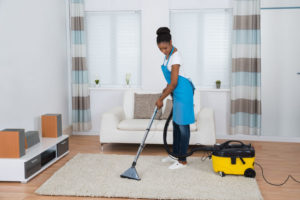 48645395 - young african woman cleaning carpet with vacuum cleaner