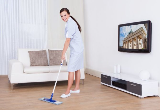 27865012 - full length portrait of young maid cleaning floor with mop at home
