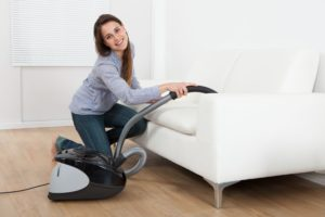 30338981 - full length side view of young woman vacuuming sofa at home
